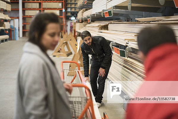 Female customer looking at salesman and man placing wooden plank on trolley in hardware store
