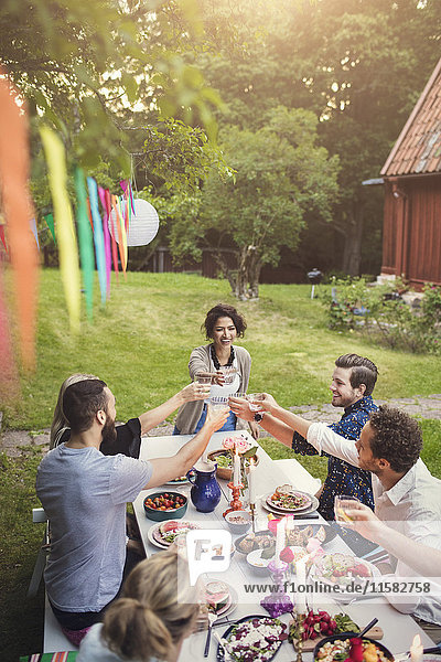 Smiling woman toasting drink with friends at table in garden party