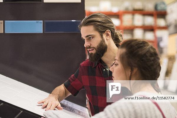 Paar untersucht Fliesen beim Einkaufen im Baumarkt
