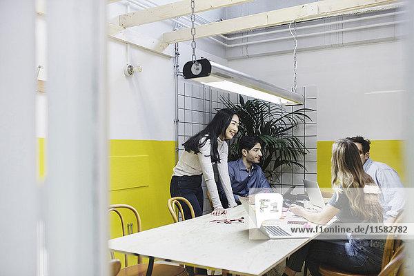 Vier Personen diskutieren im Sitzungssaal des Kreativbüros