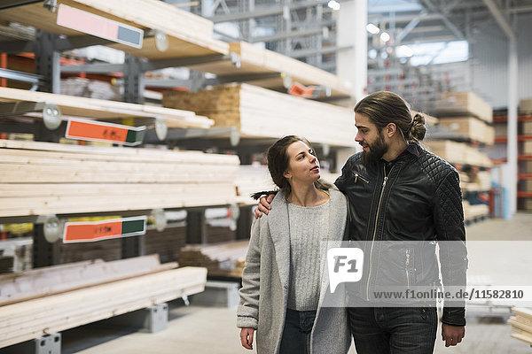 Ein Paar schaut sich an  während es im Baumarktlager spazieren geht.