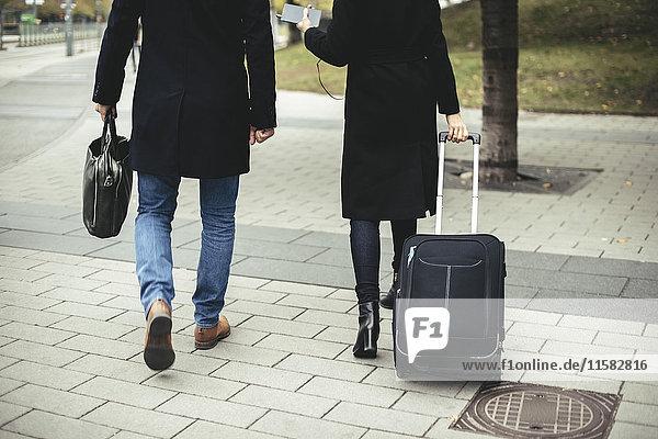 Rückansicht von Geschäftsleuten mit Gepäck auf dem Bürgersteig