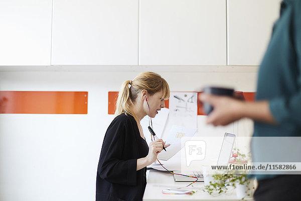Seitenansicht der mittleren erwachsenen Geschäftsfrau am Tisch mit Kollegin im Vordergrund im Büro