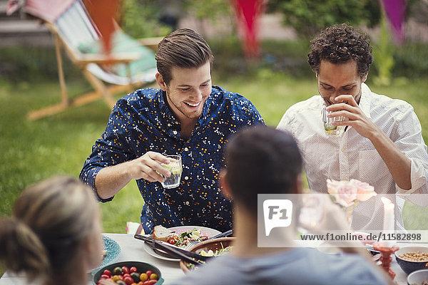 Glückliche Männer beim Trinken mit Freunden am Tisch in der Gartenparty