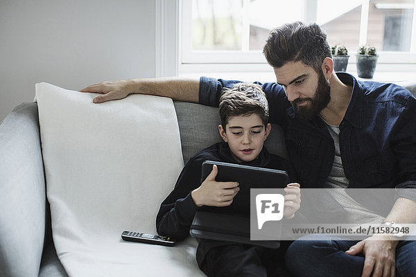 Vater schaut den Jungen mit dem digitalen Tablett an  während er auf dem Sofa im Wohnzimmer sitzt.