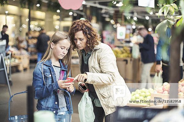 Mutter und Tochter mit Smartphone im Bioladen