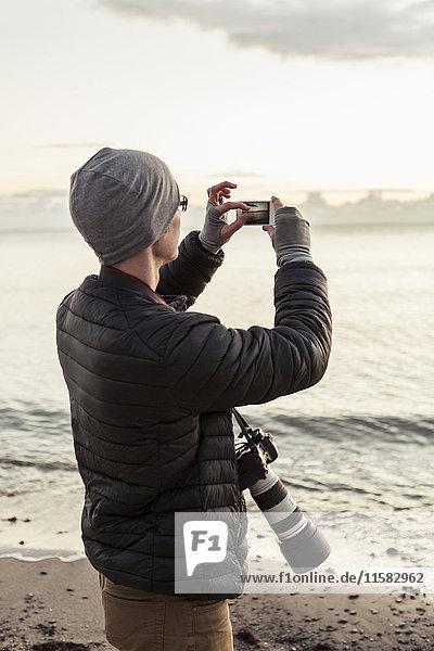 Wanderer fotografieren mit dem Smartphone am Strand