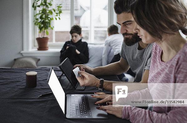 Mann und Frau online einkaufen mit Söhnen im Wohnzimmer zu Hause