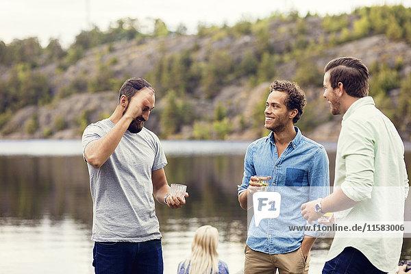 Freunde beim Reden und Trinken am Seeufer