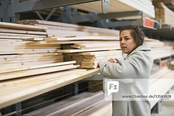 Seitenansicht der Kundin mit Holzbohle im Baumarkt