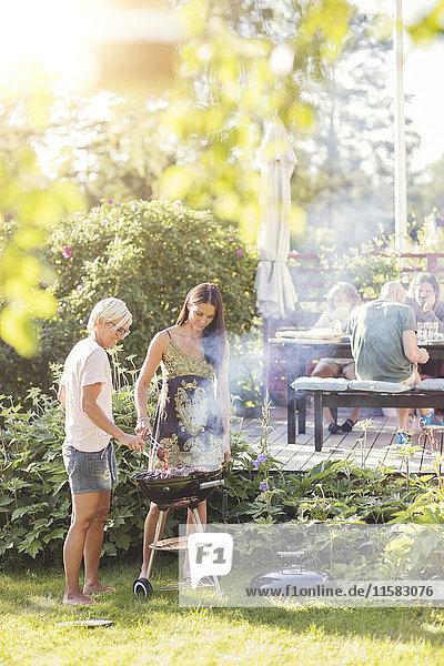 Reife Frauen beim Grillen im Garten während der Gartenparty