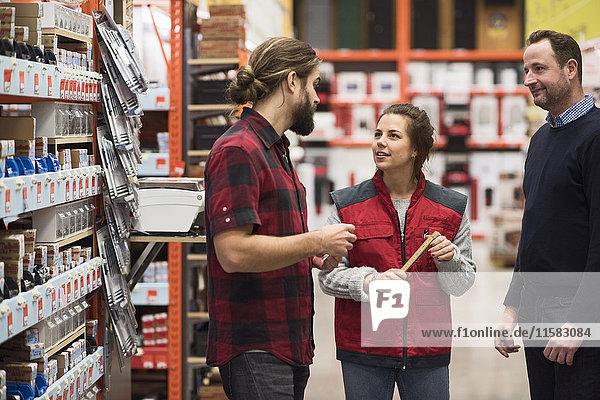 Verkäuferin im Gespräch mit männlichen Kunden im Baumarkt
