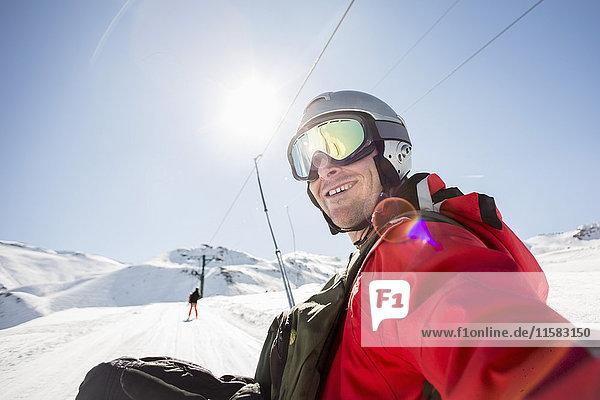 Lächelnder Mann in Skibekleidung auf schneebedecktem Feld gegen klaren Himmel