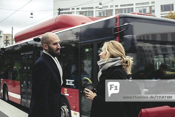 Geschäftsleute sprechen auf dem Bürgersteig mit dem Bus in der Stadt