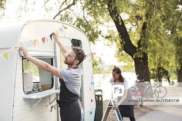 Besitzer  die außerhalb des Lebensmittelwagens auf der Straße arbeiten.