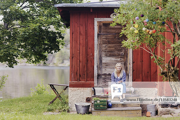 Lächelnde Frau mit Bio-Gemüse sitzend vor Holzhäuschen
