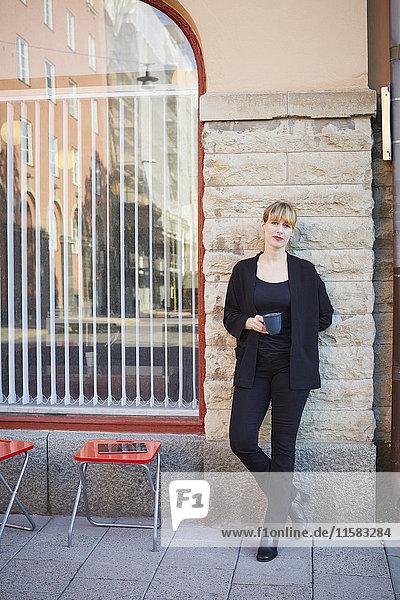 Vollständiges Porträt einer selbstbewussten Geschäftsfrau  die eine Kaffeetasse außerhalb des Büros hält.