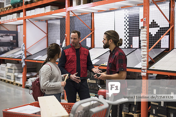 Salesman discussing with couple by shelves at hardware store