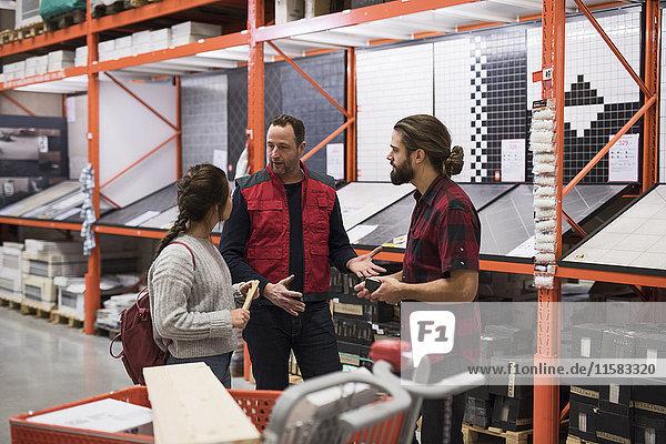 Verkäufer bespricht mit Paar bei Regalen im Baumarkt