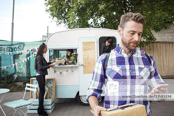 Männlicher Kunde mit Smartphone auf der Straße mit Lebensmittel-LKW-Besitzer und Frau im Hintergrund