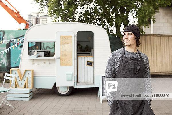 Nachdenklicher männlicher Besitzer  der wegguckt  während er vor dem Essenstruck auf der Straße steht.