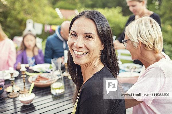 Porträt einer glücklichen Frau  die mit Familie und Freunden am Esstisch im Garten sitzt.