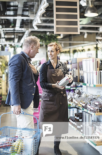 Verkäuferin erklärt Produkt dem reifen Mann im Bio-Supermarkt