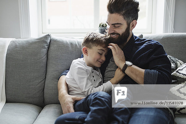 Vater und Sohn sitzen zu Hause auf dem Sofa.