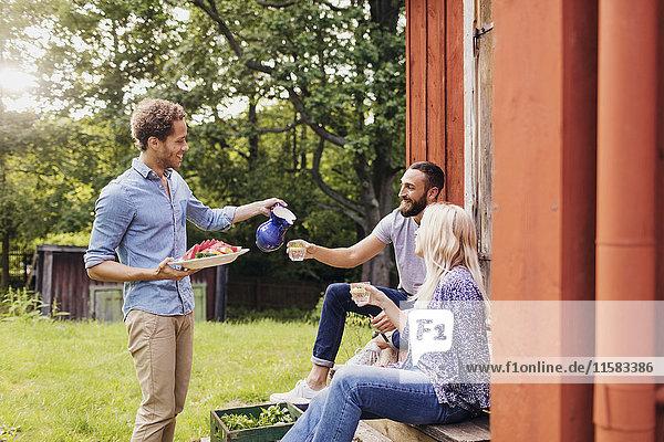 Mann hält Salatschale und serviert Freunden ein Getränk