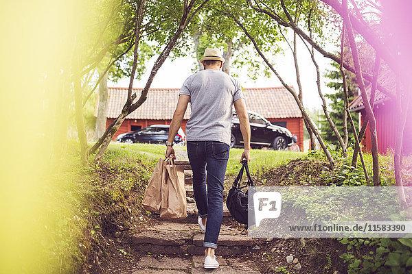 Rückansicht des Mannes mit Gepäckklettertreppe im Hinterhof