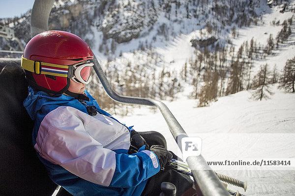 Seitenansicht des im Skilift fahrenden Jungen