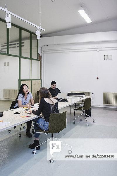 Zwei Frauen diskutieren am Schreibtisch im Kreativbüro