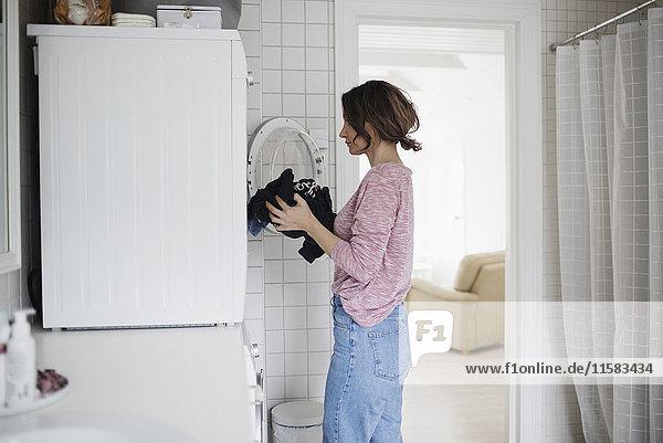 Seitenansicht der Frau beim Laden der Wäsche in der Waschmaschine zu Hause