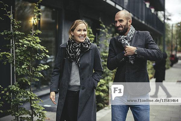 Lächelnder Geschäftsmann und Geschäftsfrau im Gespräch auf dem Bürgersteig