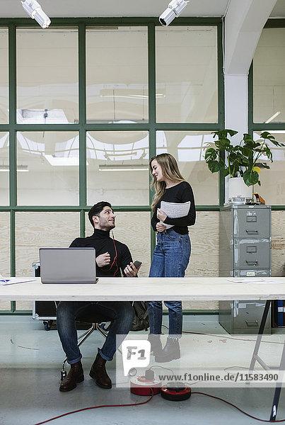 Zwei Kollegen im Gespräch am Schreibtisch im Büro