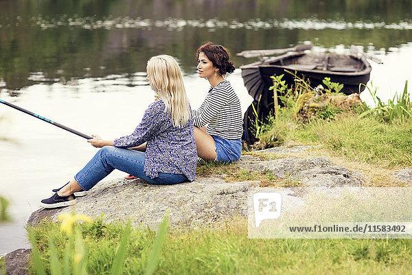 Volle Länge der Frauen beim Angeln am Seeufer