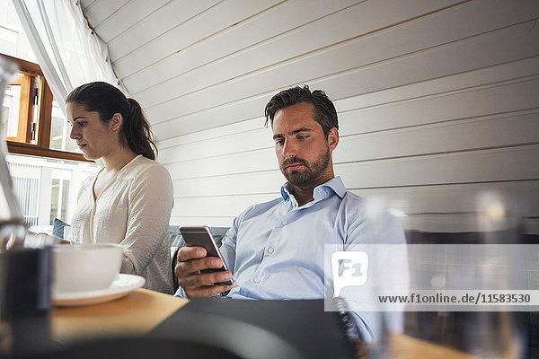 Mittlerer erwachsener Geschäftsmann mit Smartphone von Kollegin im Büro