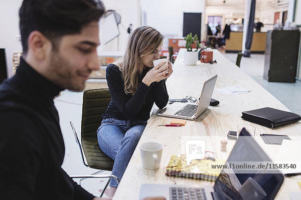 Junge Frau beim Kaffeetrinken mit Kollegin am Schreibtisch im Büro