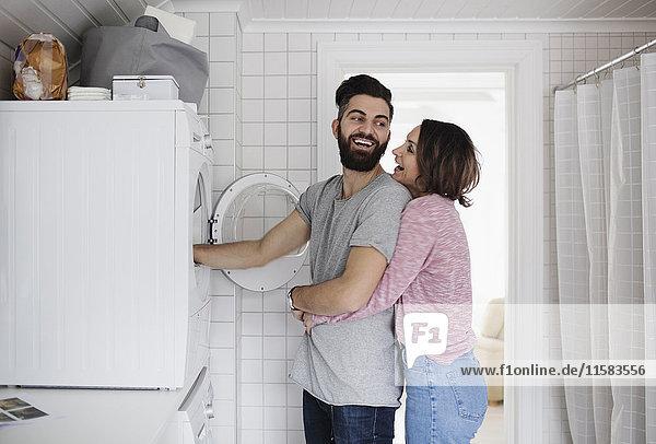 Glückliches Paar steht an der Waschmaschine zu Hause