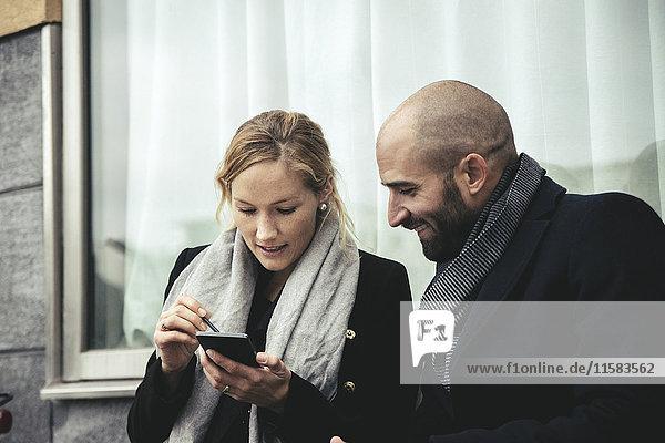 Lächelnde Geschäftsfrau betrachtet Geschäftsfrau mit Smartphone gegen Fenster