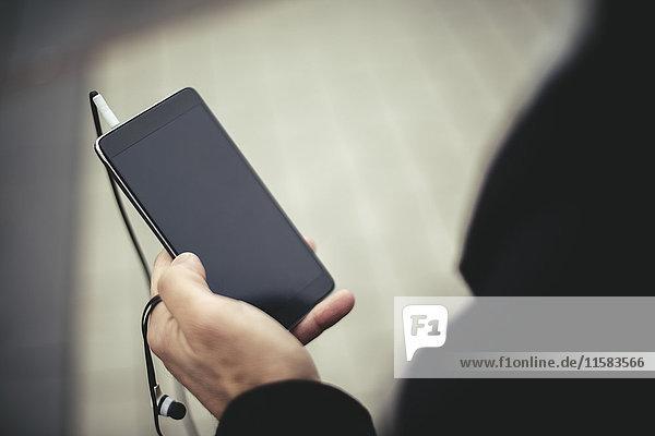 Beschnittenes Bild des Geschäftsmannes mit dem Handy auf der Stadtstraße