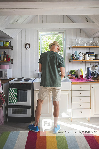 Rückansicht des Mannes  der zu Hause in der Küche arbeitet