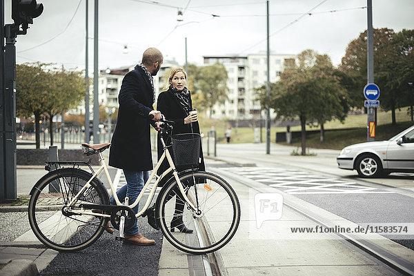 Geschäftsleute mit Fahrrad über die Stadtstraße