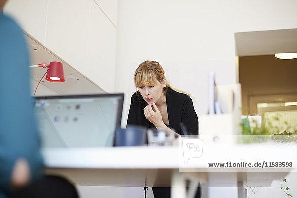 Mittlere erwachsene Geschäftsfrau bei der Arbeit am Tisch im Büro