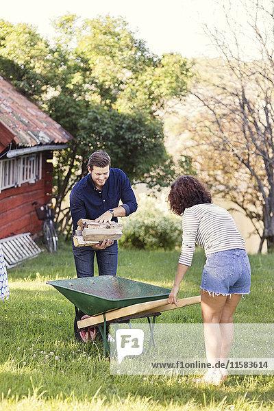 Mann stellt Brennholz  während die Frau an einem sonnigen Tag eine Schubkarre auf dem Hof hält.