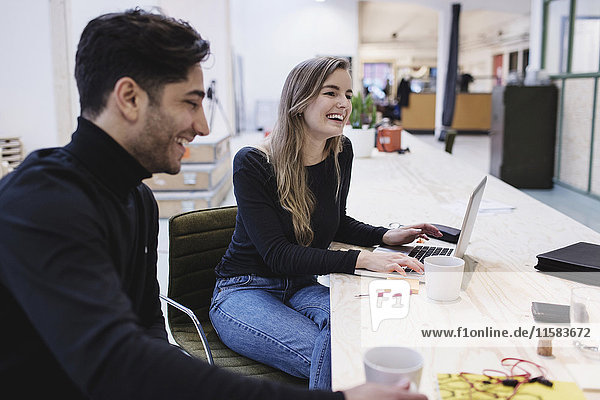 Cheerful woman and man sitting at desk in office