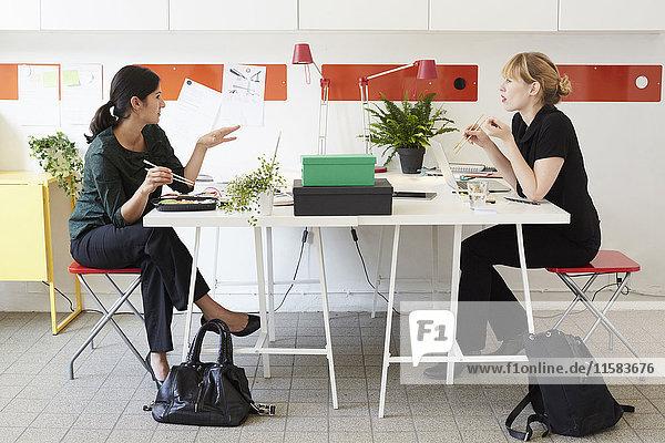 Volle Länge der Geschäftsfrauen beim Mittagessen am Tisch im Büro