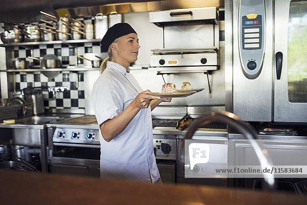 Köchin serviert Essen in der Küche des Restaurants