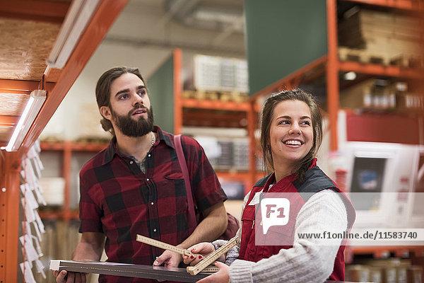 Glückliche Verkäuferin schaut weg  während sie mit einem männlichen Kunden im Baumarkt steht.