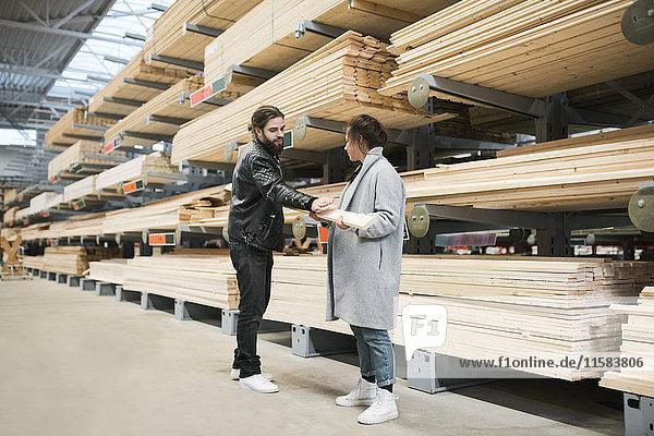 Paar beim Betrachten von Holzbrettern in den Regalen des Baumarktes